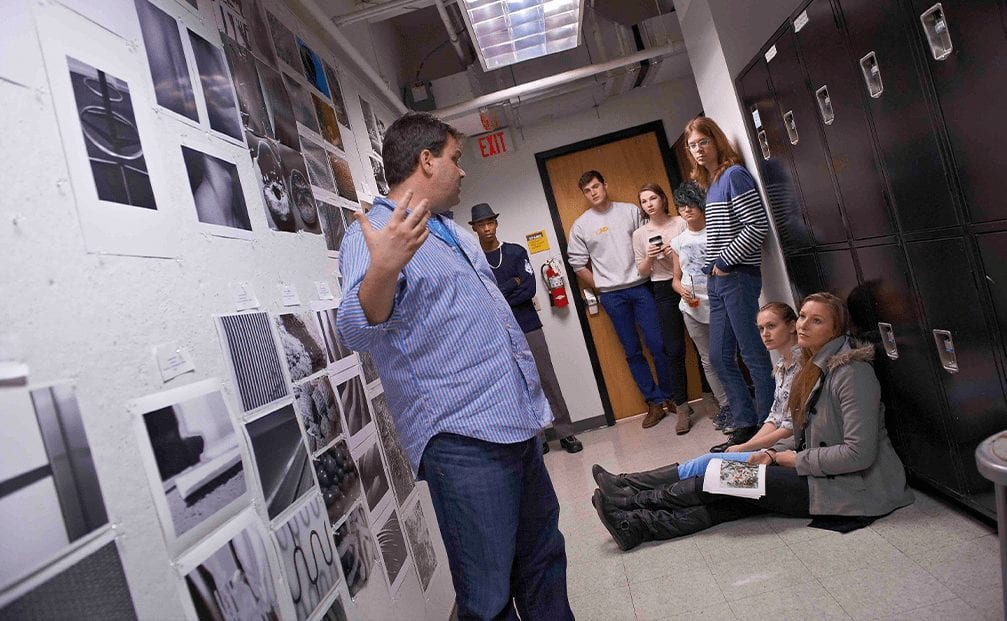 Students listen to professor critique their photography assignments