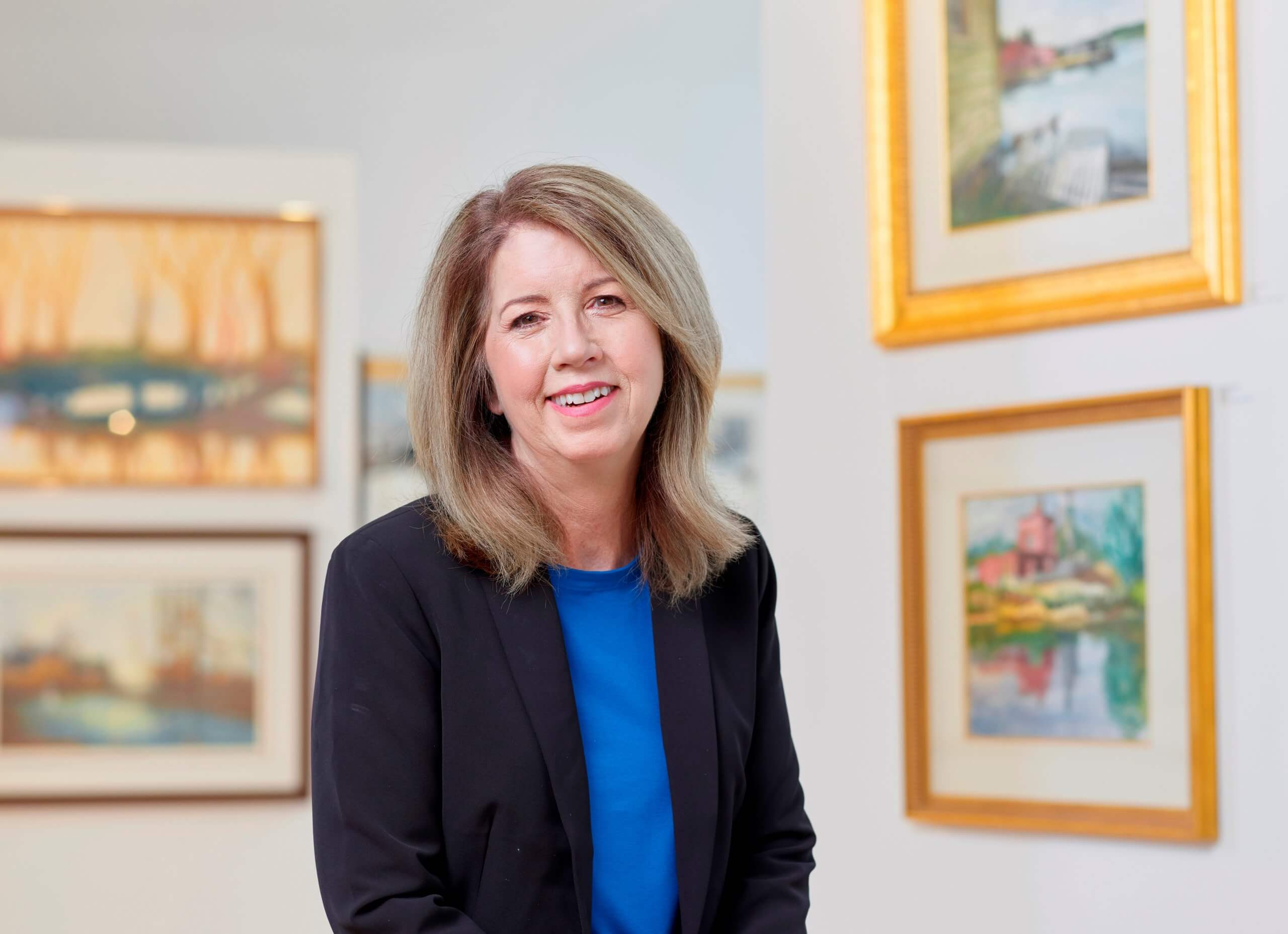 President Jean Dahlgren poses for a picture inside of a gallery